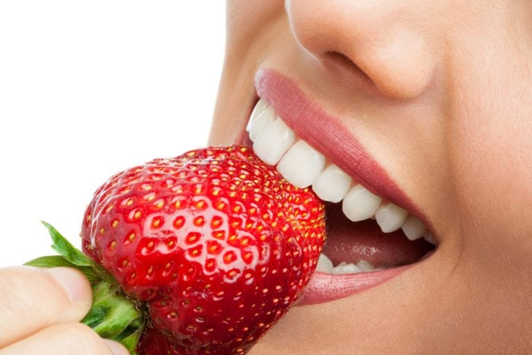 Close-up of a smiling mouth eating a strawberry